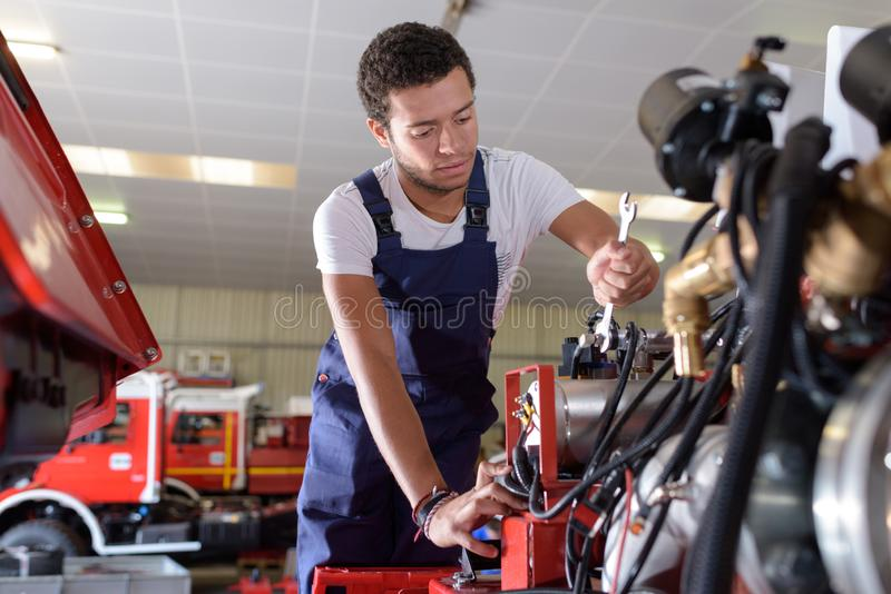 Close-up auto mechanic repairing lorry engine stock images