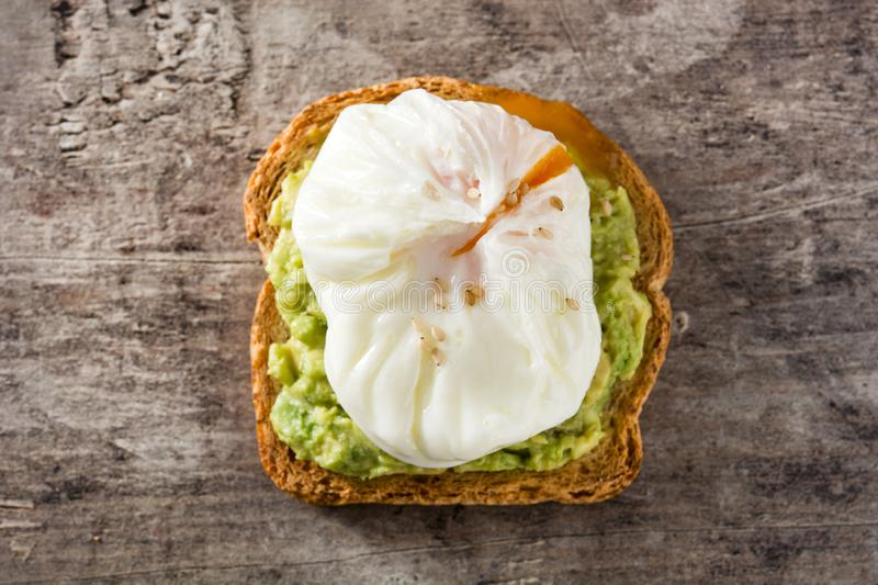 Close up avocado toast with poached egg on wood royalty free stock photography