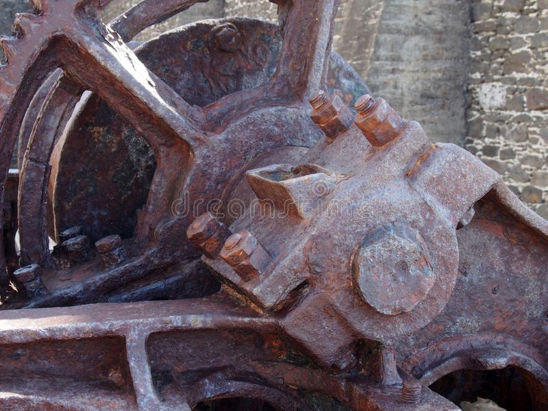 Close up of an axle and broken spoked wheel on old rusted abandoned industrial machinery against a stone wall stock images