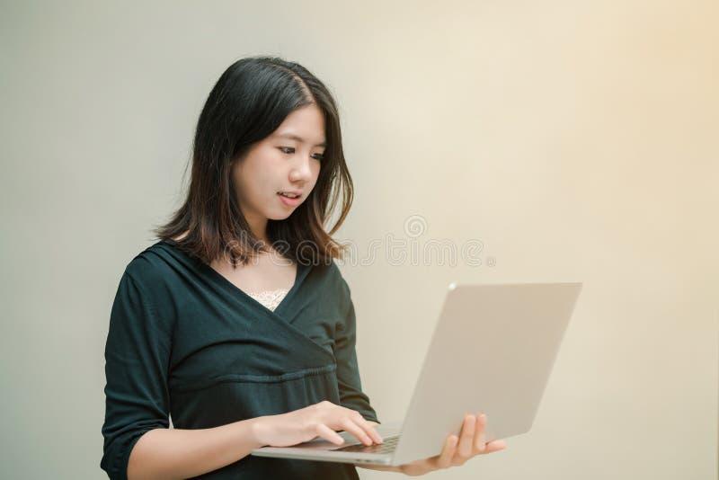 Close-up Aziatische mooie vrouw die een zwart overhemd dragen die zich rond het grijze muurgebruik een laptop computer bevinden o stock fotografie