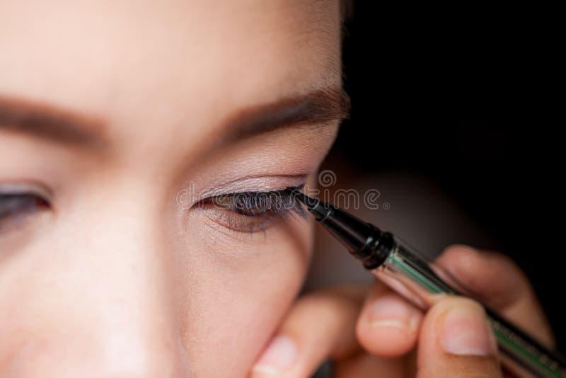 Close-up Aziatische vrouw die eyeliner op oog toepassen royalty-vrije stock foto