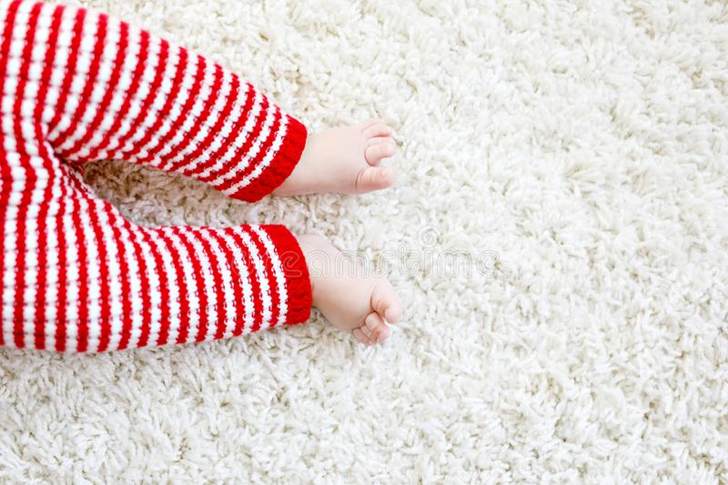 Close-up of baby body and legs in red Santa Clause trousers on Christmas stock images