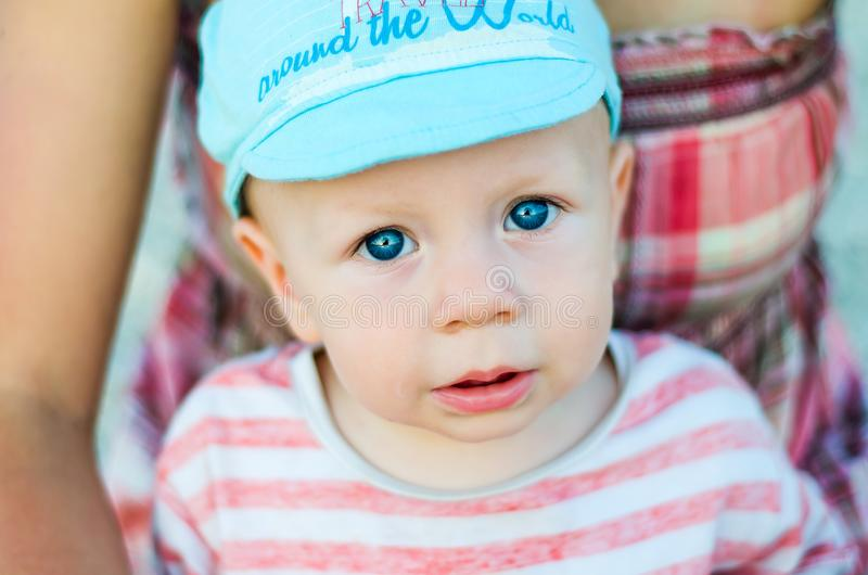 Close up of baby boy face with blue eyes with open mouth and blue cap. Child and children emotions stock photos