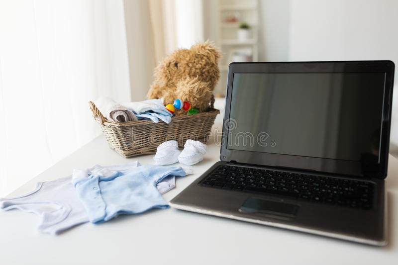 Close up of baby clothes, toys and laptop at home. Babyhood, motherhood, clothing, technology and object concept - close up of baby clothes and toys for newborn stock photo