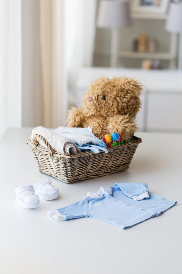 Close up of baby clothes and toys for newborn. Babyhood, motherhood, clothing and object concept - close up of baby clothes and toys for newborn boy in basket at royalty free stock image