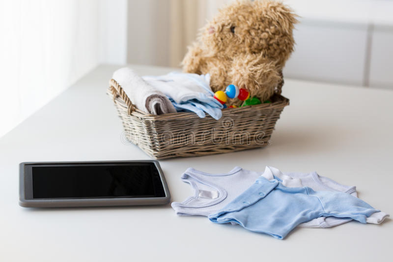 Close up of baby clothes, toys and tablet pc. Babyhood, motherhood, clothing, technology and object concept - close up of baby clothes and toys for newborn boy stock image