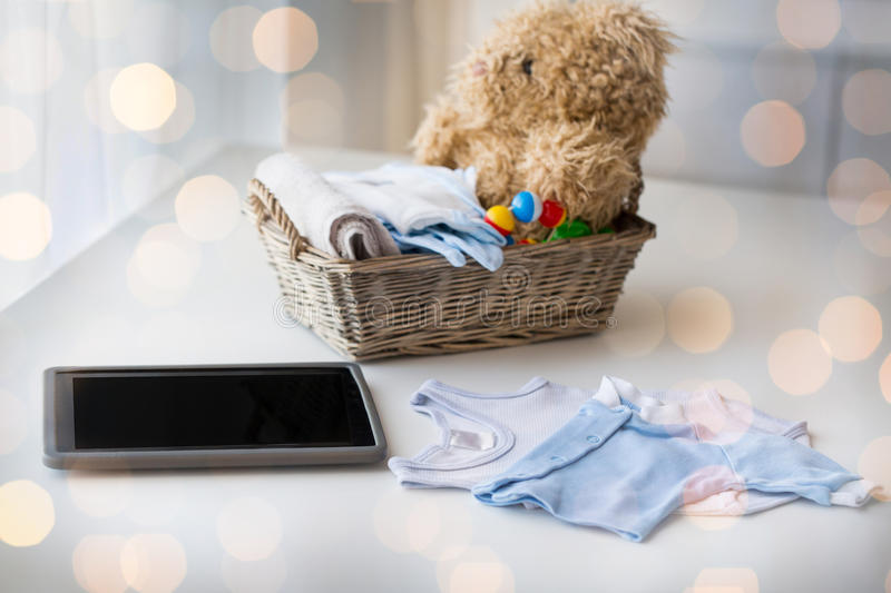 Close up of baby clothes, toys and tablet pc. Babyhood, motherhood, clothing, technology and object concept - close up of baby clothes and toys for newborn boy royalty free stock photos