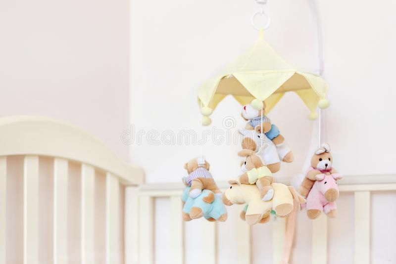 Close-up baby crib with musical animal mobile at nursery room. Hanged developing toy with plush fluffy animals. Happy parenting an. D childhood, expectation royalty free stock image