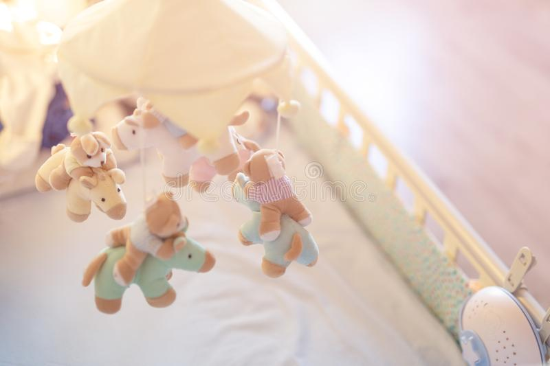 Close-up baby crib with musical animal mobile at nursery room. Hanged developing toy with plush fluffy animals. Happy parenting an stock photo