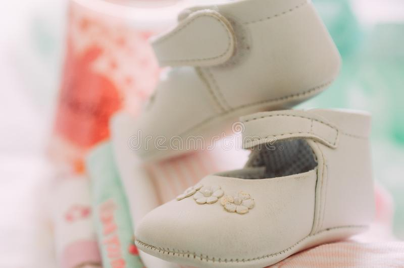 Close up of baby girl elegant white shoes with warm modern colors and style during babyshower royalty free stock image