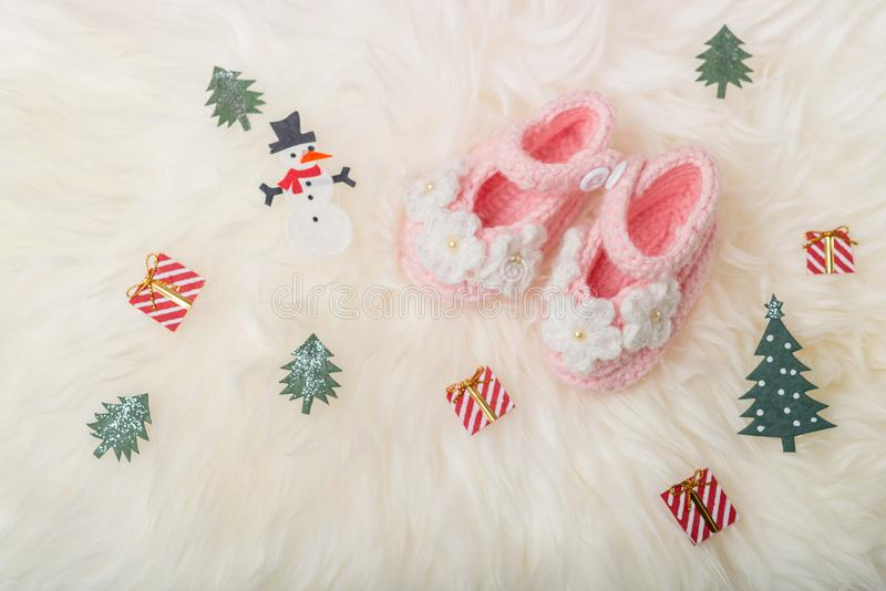 Close up Baby girl knitted shoes on white blanket background.Merry christmas and happy new year greeting card with copy-space. stock image