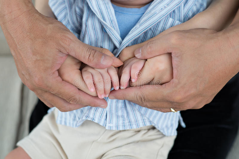 The happiest!. Close-up baby's hands into parents hands royalty free stock photo