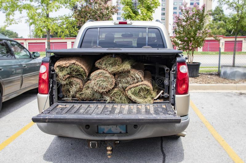 Close-up of back of pickup truck with bed protector and rolls of sod in the back with the tailgate down. A Close-up of back of pickup truck with bed protector stock photo