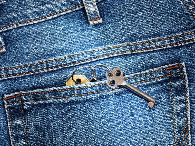 Close-up back pocket jeans with house keys stock photography