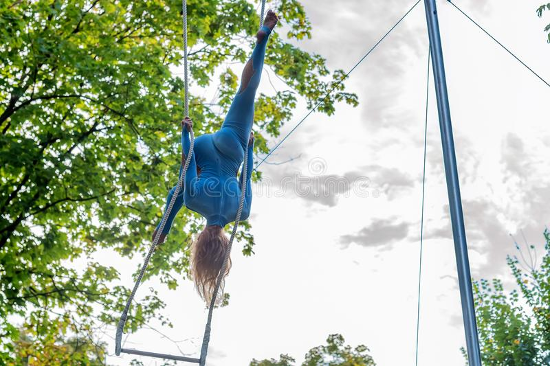 Back view young attractive female trapeze artist. Close up back view of a blond woman in costume standing on rapeze outdoors stock photo