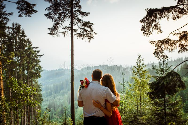 Close-up back view of the pretty hugging couple enjoying the sunset in the mountains. No face. Romantic portrait. Close-up back view of the pretty hugging royalty free stock photos
