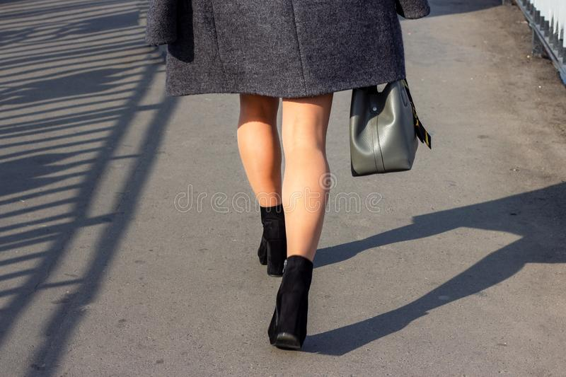 Close up back view of a pretty young woman legs walking down the street in the autumn on a modern city background. stock images