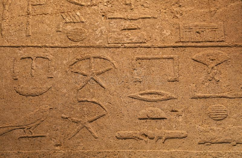 Stone wall with ancient Egyptian hieroglyphs. Close up background of antique stone wall with carved ancient Egyptian hieroglyphs, front view stock photos