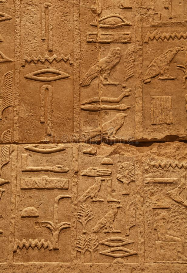 Stone wall with ancient Egyptian hieroglyphs. Close up background of antique stone wall with carved ancient Egyptian hieroglyphs, front view royalty free stock photo