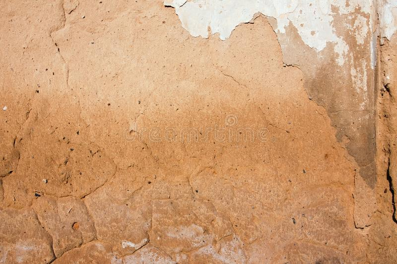 Close-up background of plaster covered shabby old worn wall, horizontal rough abstract surface texture. Close-up background of bright orange plaster covered stock photography