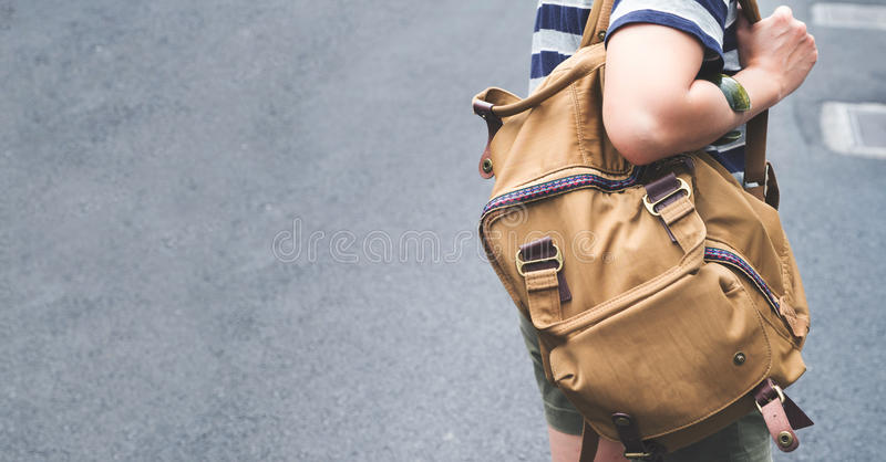 Close up backpack at back of woman traveler walking on street to royalty free stock photo