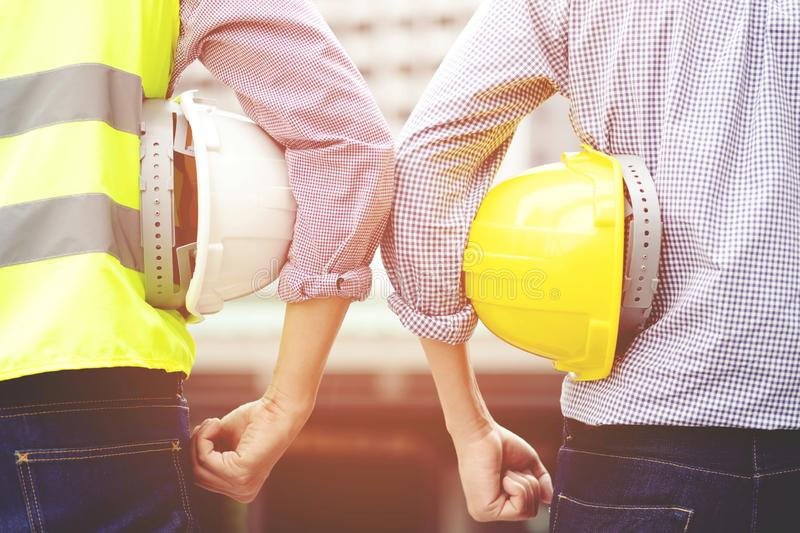 Close up backside view of engineering male construction worker stand holding safety helmet royalty free stock photos
