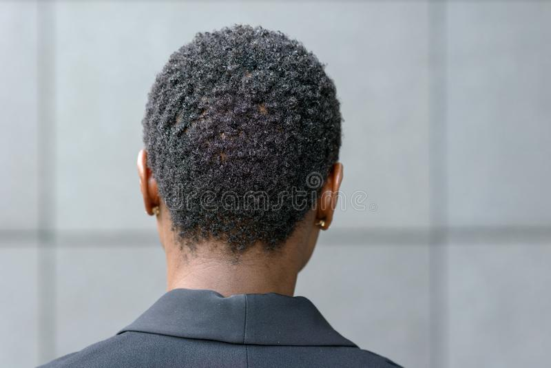 Close up back side portrait of young black woman. Close up backview portrait of young black woman with short haircut and small earrings, wearing black blazer royalty free stock image