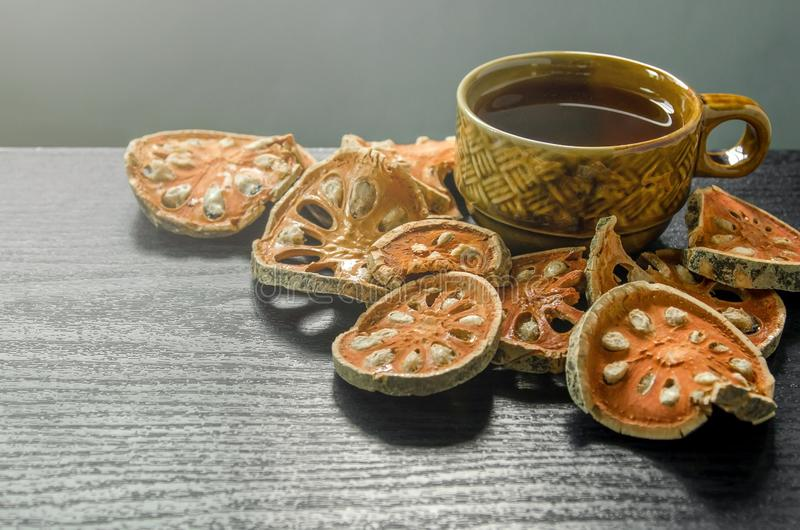 Close-up of bael dry and glass tea and bael juice on the wooden floor stock photos