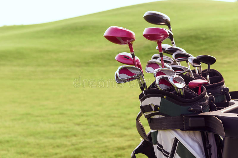 Close up of bag with golf clubs. Fully equipped. Close up of bag full of different golf clubs on background of green course stock photo