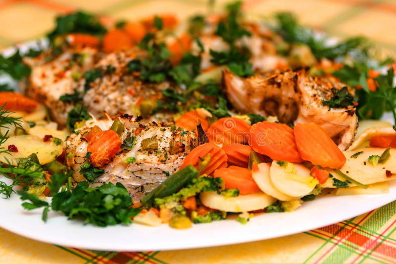 Close-up of baked fish pieces with vegetables royalty free stock image