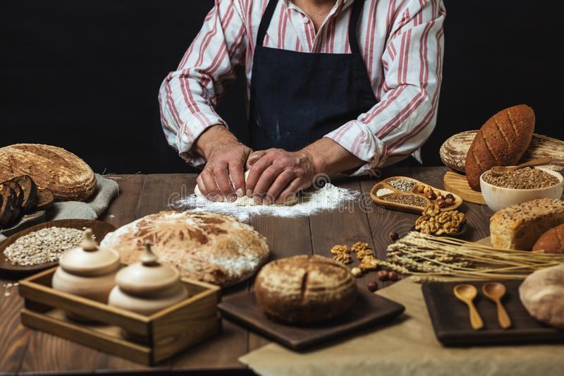 Close up of baker hands kneading dough and making bread with a rolling pin. stock image