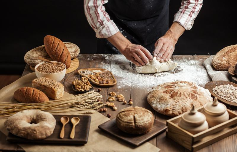 Close up of baker hands kneading dough and making bread with a rolling pin. Chef or baker, dressed in black apron, preparing a portion of fresh dough in rural stock images