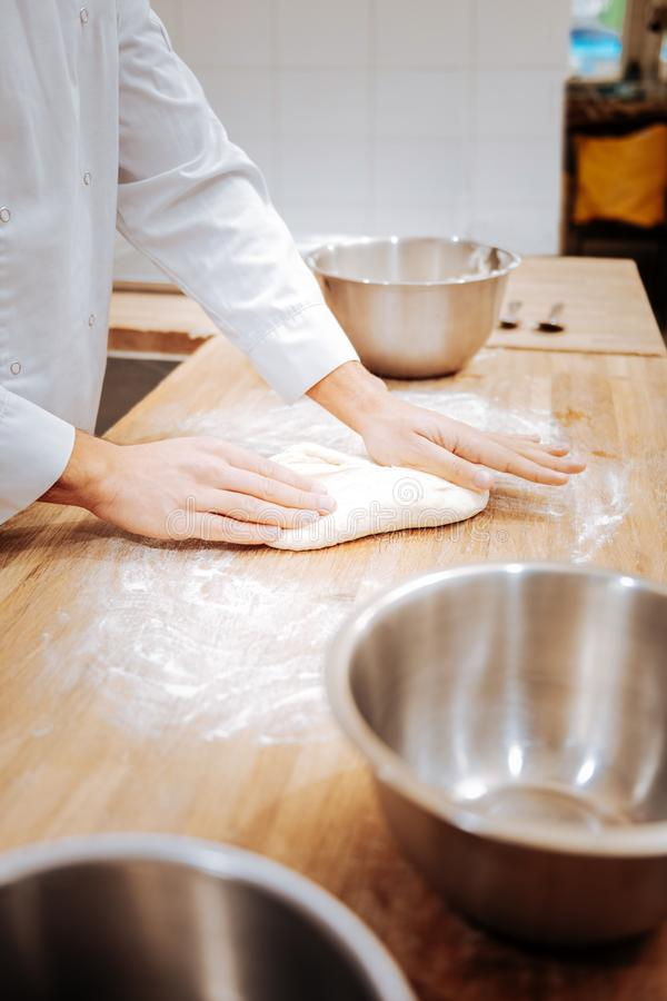 Close up of baker kneading dough on the table in the morning. Dough on table. Close up of professional young baker kneading dough on the table in the morning stock photo