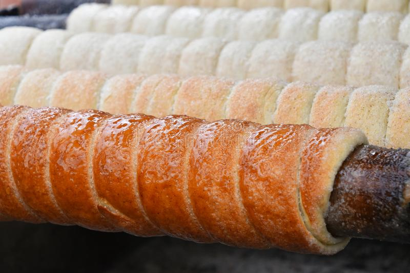 Close up baking chimney cake on grill. Close up sweet Trdelnik baking on grill, this spit cake is popular in Europe, Austria, Hungary, Slovakia and Czech stock photos