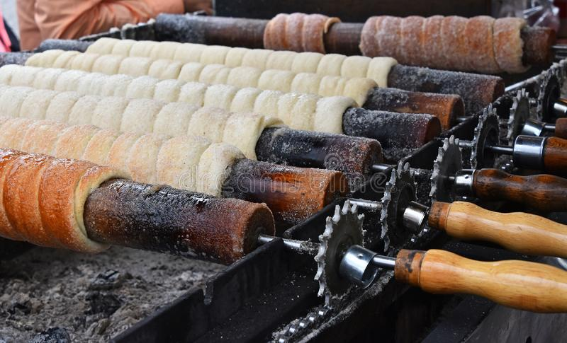 Close up baking chimney cake on grill. Close up sweet Trdelnik baking on grill, this spit cake is popular in Europe, Austria, Hungary, Slovakia and Czech royalty free stock photos