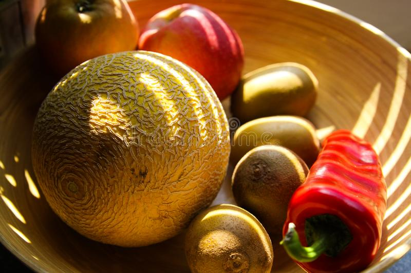 Close up bamboo fruit basket with melon, apples, kiwis, bell pepper illuminated by evening sun beams. German kitchen stock image