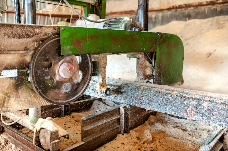 Close-up of band saw sawmill. Industrial wood production factory - close-up of band saw sawmill cutting wood stock image