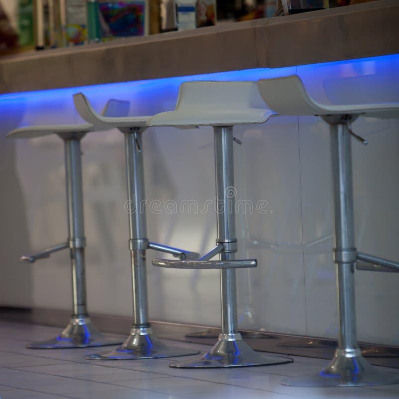 Close-Up of Bar Stools at Illuminated Bar stock images