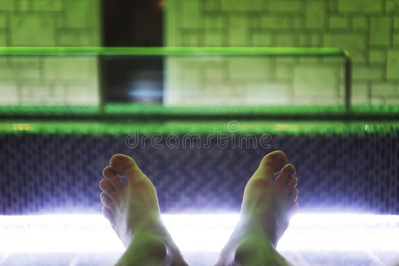 A close up of barefooted man lying down near indoor luxury swimming pool. A shot of young man's feet at the indoor pool backgroun royalty free stock photo