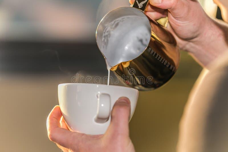 Close up Barista em preparar a espuma de derramamento do leite do cappuccino apropriado em um copo imagem de stock