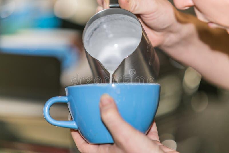 Close up Barista em preparar a espuma de derramamento do leite do cappuccino apropriado em um copo fotos de stock