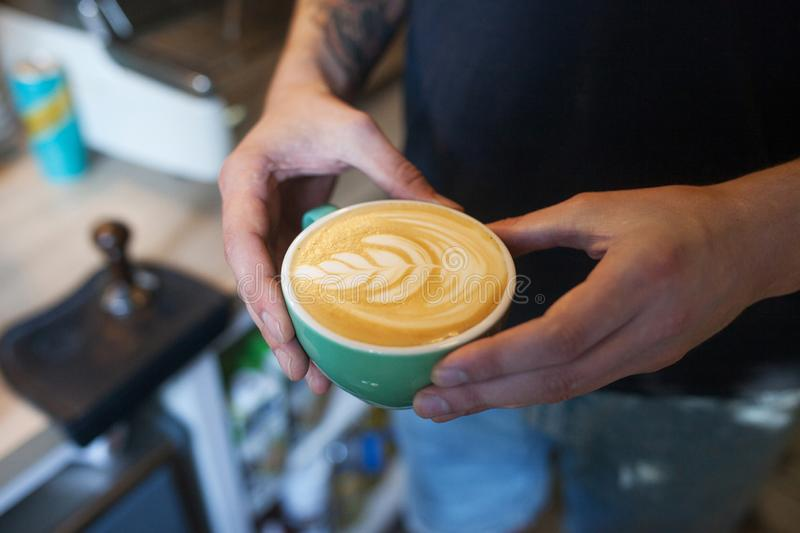 Close up of barista holding aromatic cappuccino. Coffee ready for sale. Male hands holding a cup of coffee royalty free stock photos