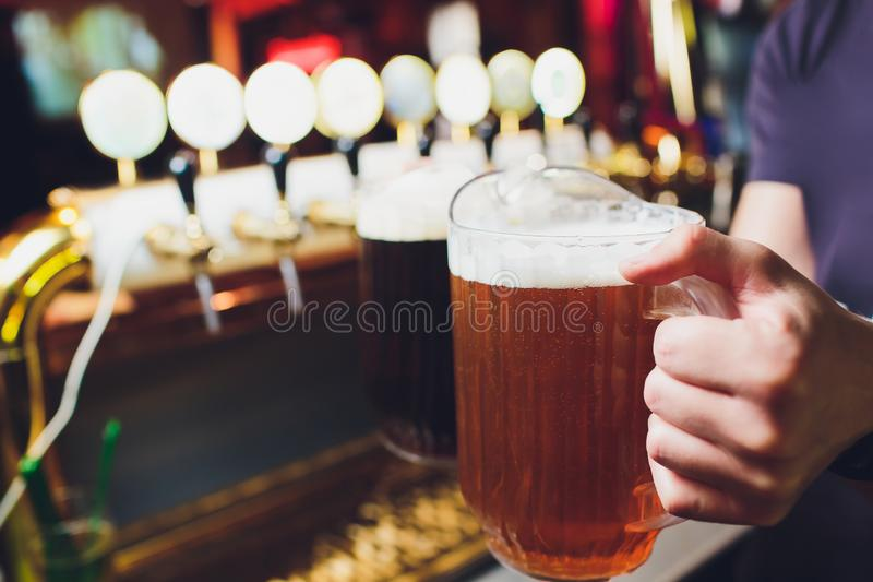 Close-up of barman hand at beer tap pouring a draught lager beer. Close-up of barman hand at beer tap pouring a draught lager beer royalty free stock image