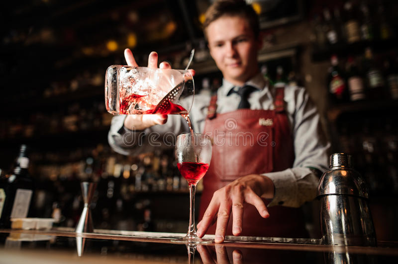 Close up bartender pouring bright red alcohol cocktail into fancy glass. Close up of bartender pouring bright red alcohol cocktail into the glass royalty free stock photo