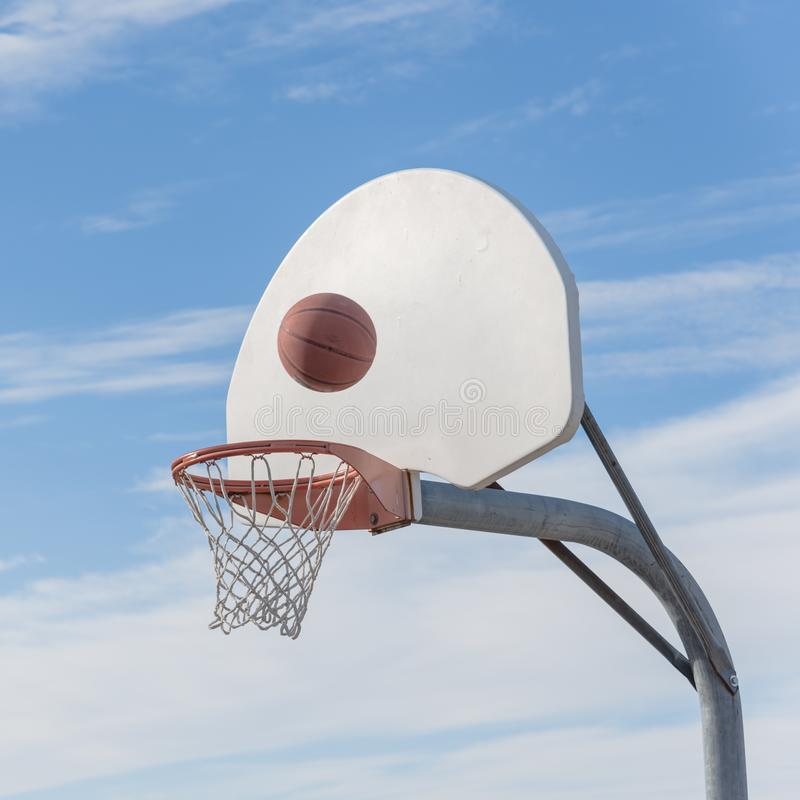 Close-up basketball hoop rim and backboard under cloud blue sky stock photography