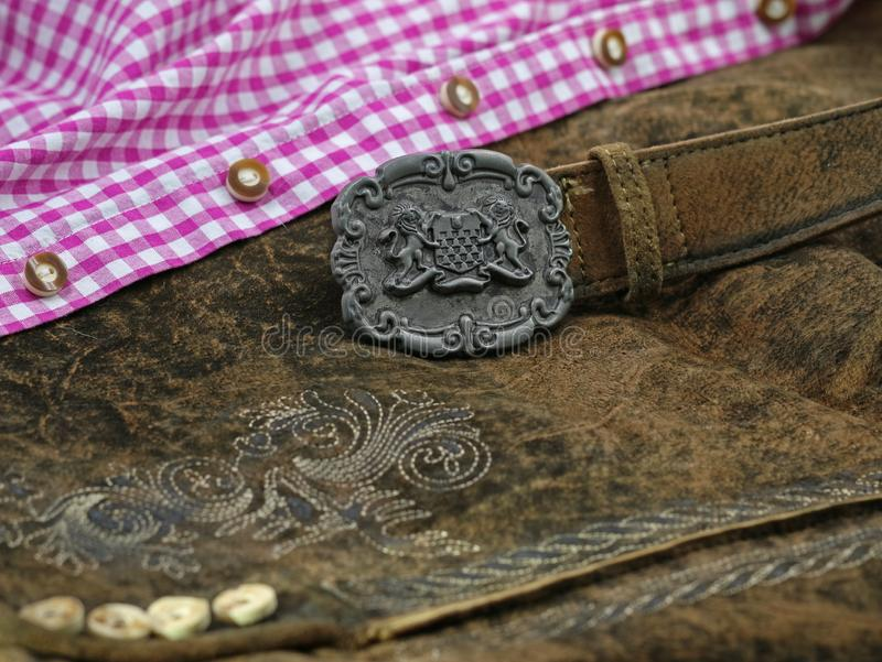 Close up bavarian lether belt with coat of arms on lederhose and pink check shirt, traditional clothing for Oktoberfest royalty free stock photography