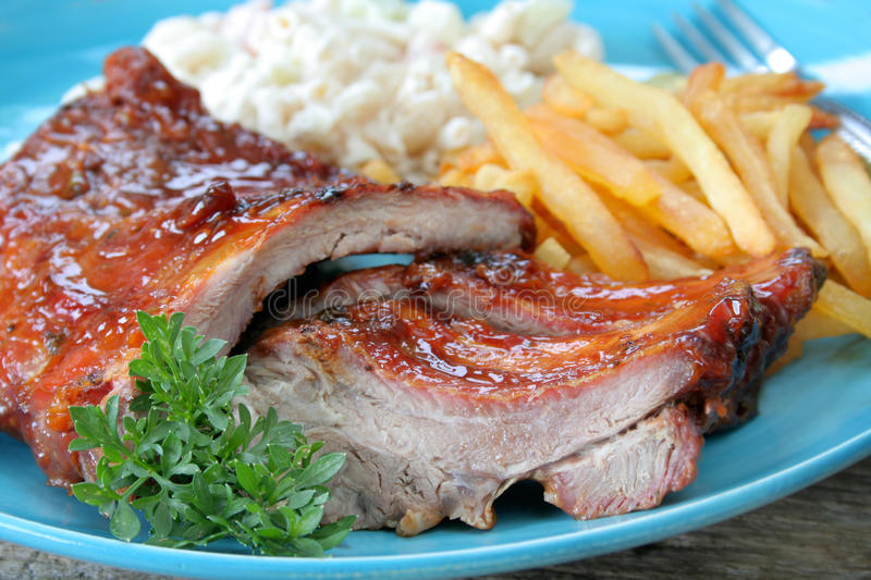 Close up BBQ Ribs. Plate of BBQ ribs along with sides of french fries and macaroni salad and garnished with fresh parsley stock photos