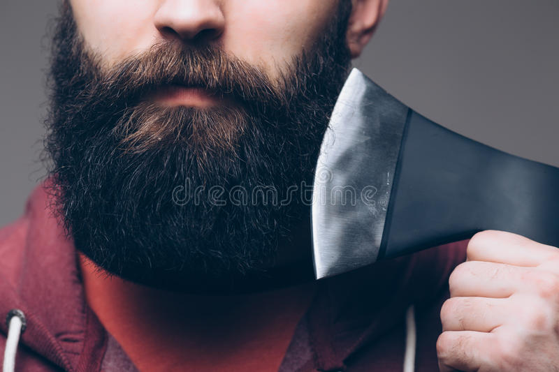 Close up of beard Confident young bearded man carrying a big axe stock image