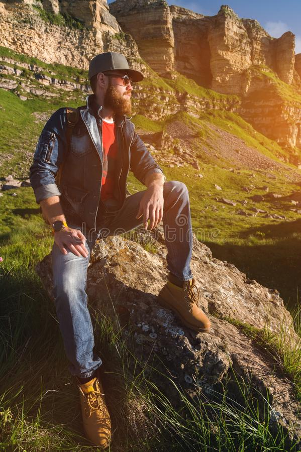 Close-up of a bearded man in jeans clothes in sunglasses and a cap with a backpack sitting at the foot of the epic rocks royalty free stock photography