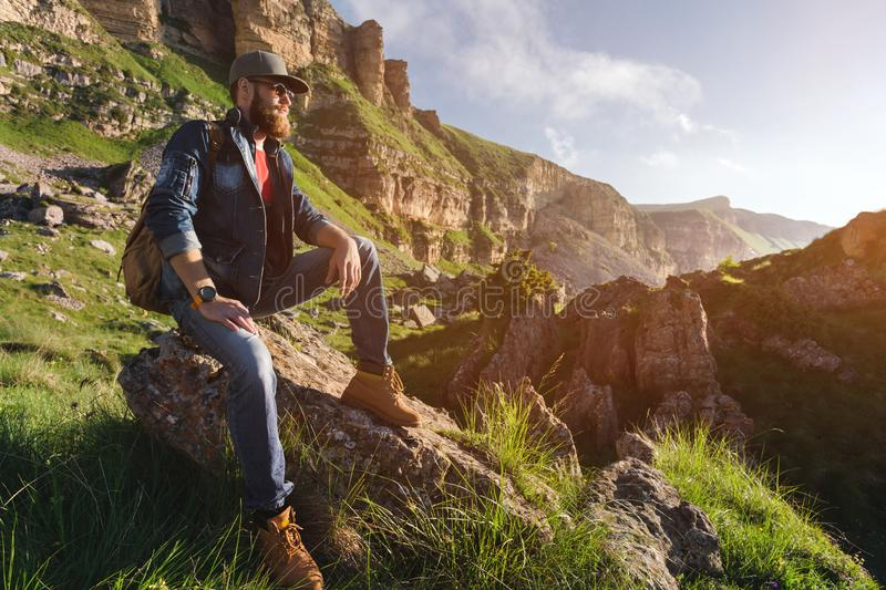 Close-up of a bearded man in jeans clothes in sunglasses and a cap with a backpack sitting at the foot of the epic rocks royalty free stock photo